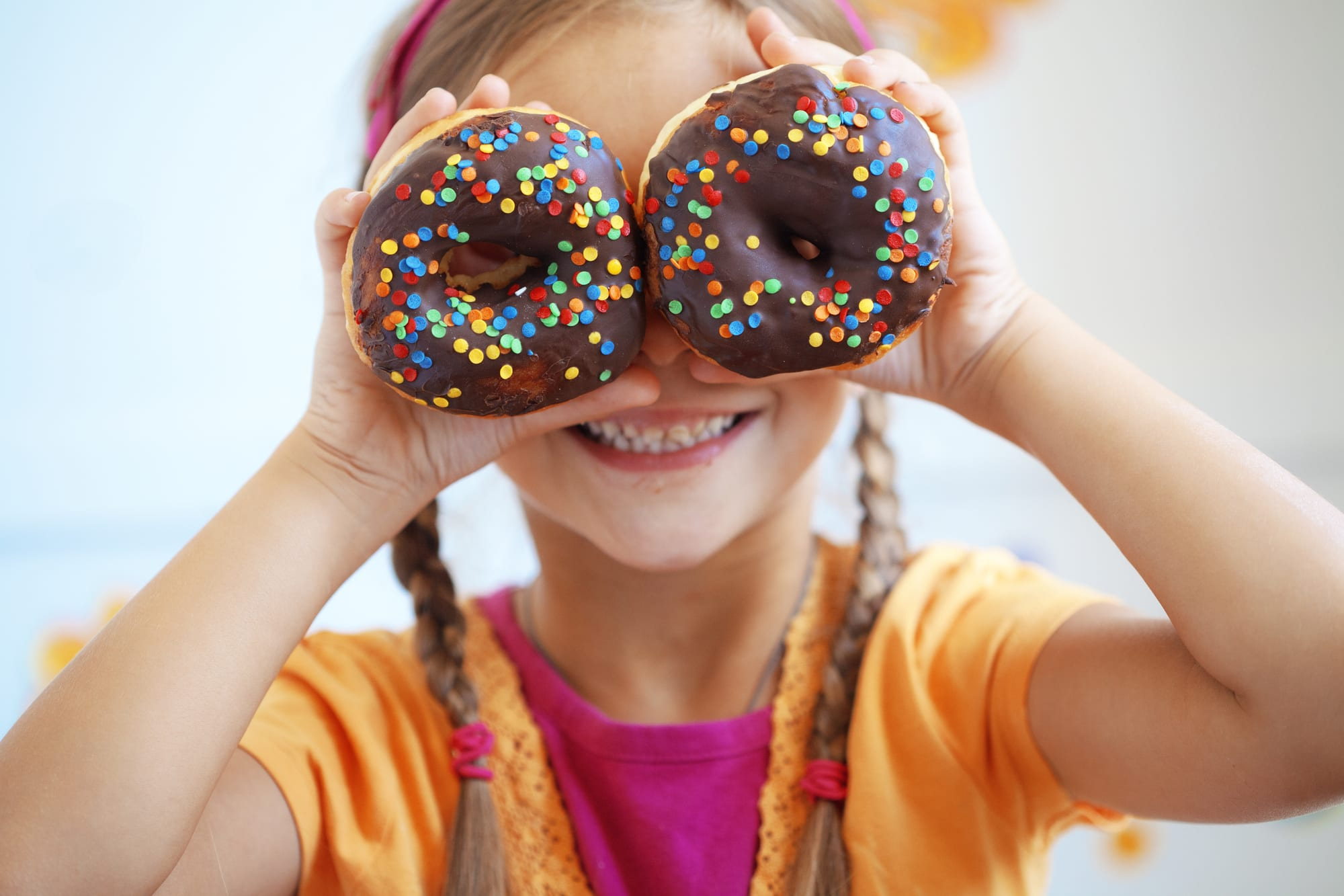 little girl holding donuts over her eyes