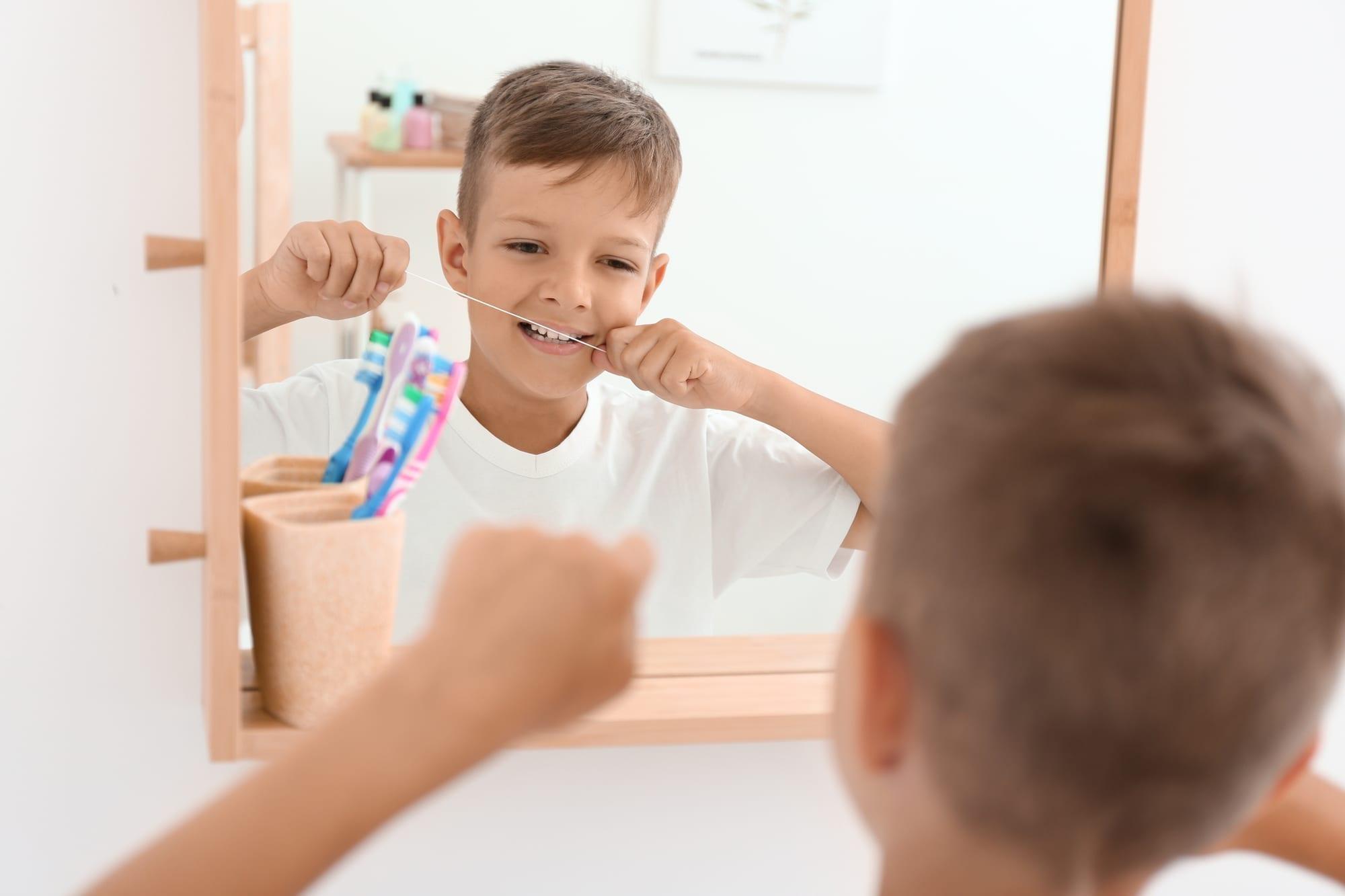 Little boy flossing teeth in bathroom mirror