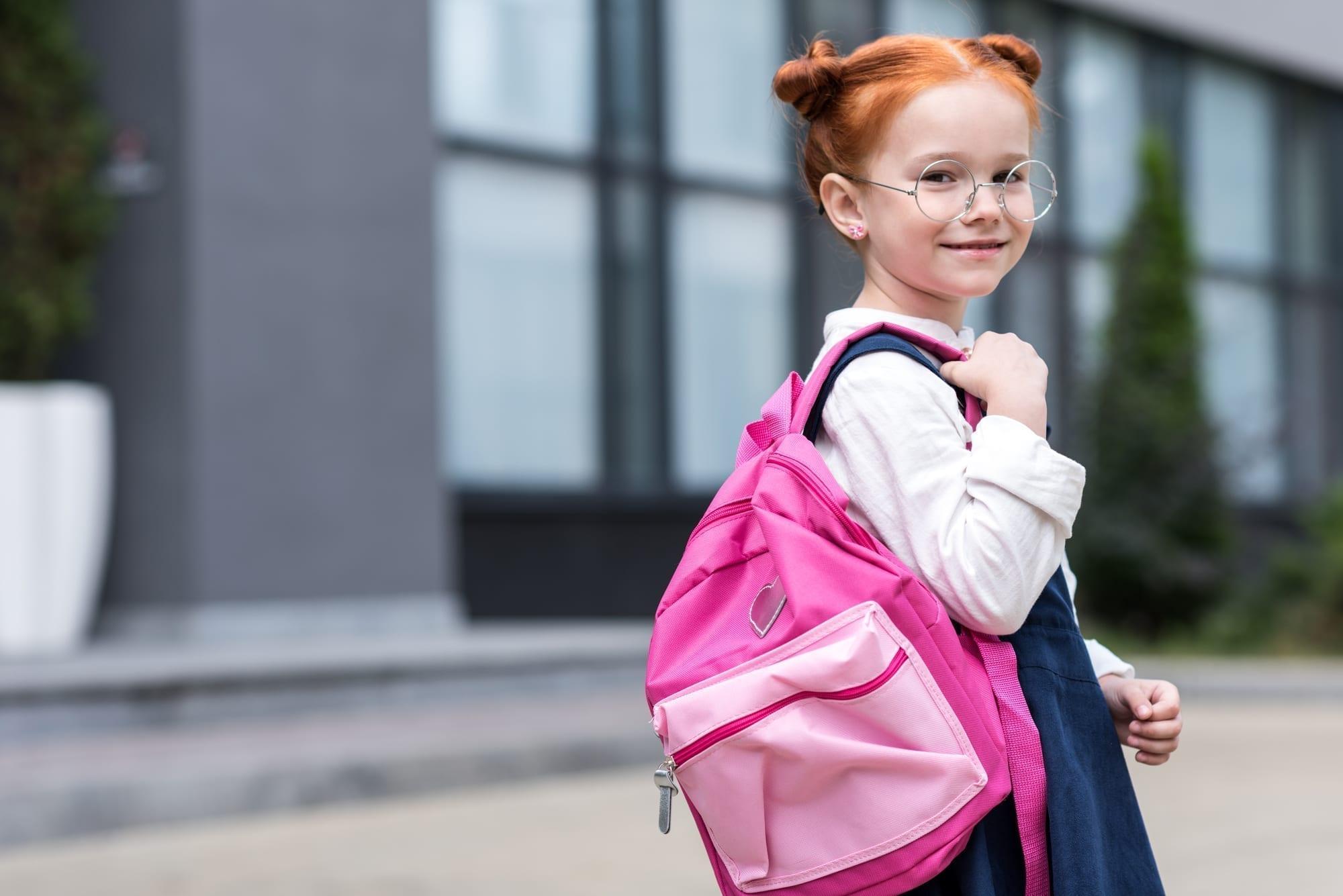 little girl holding backpack over shoulder