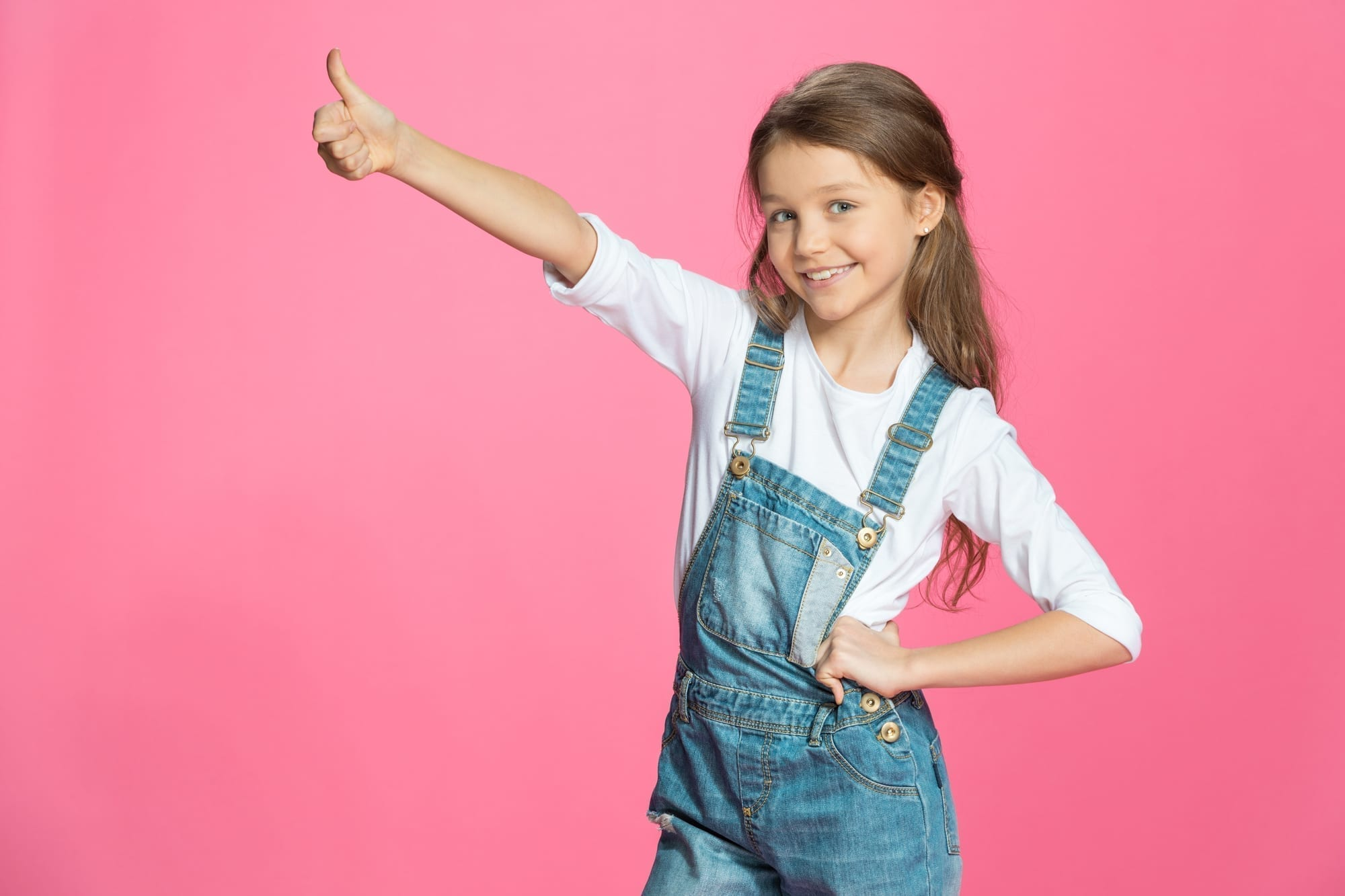 little girl with thumbs up on pink background