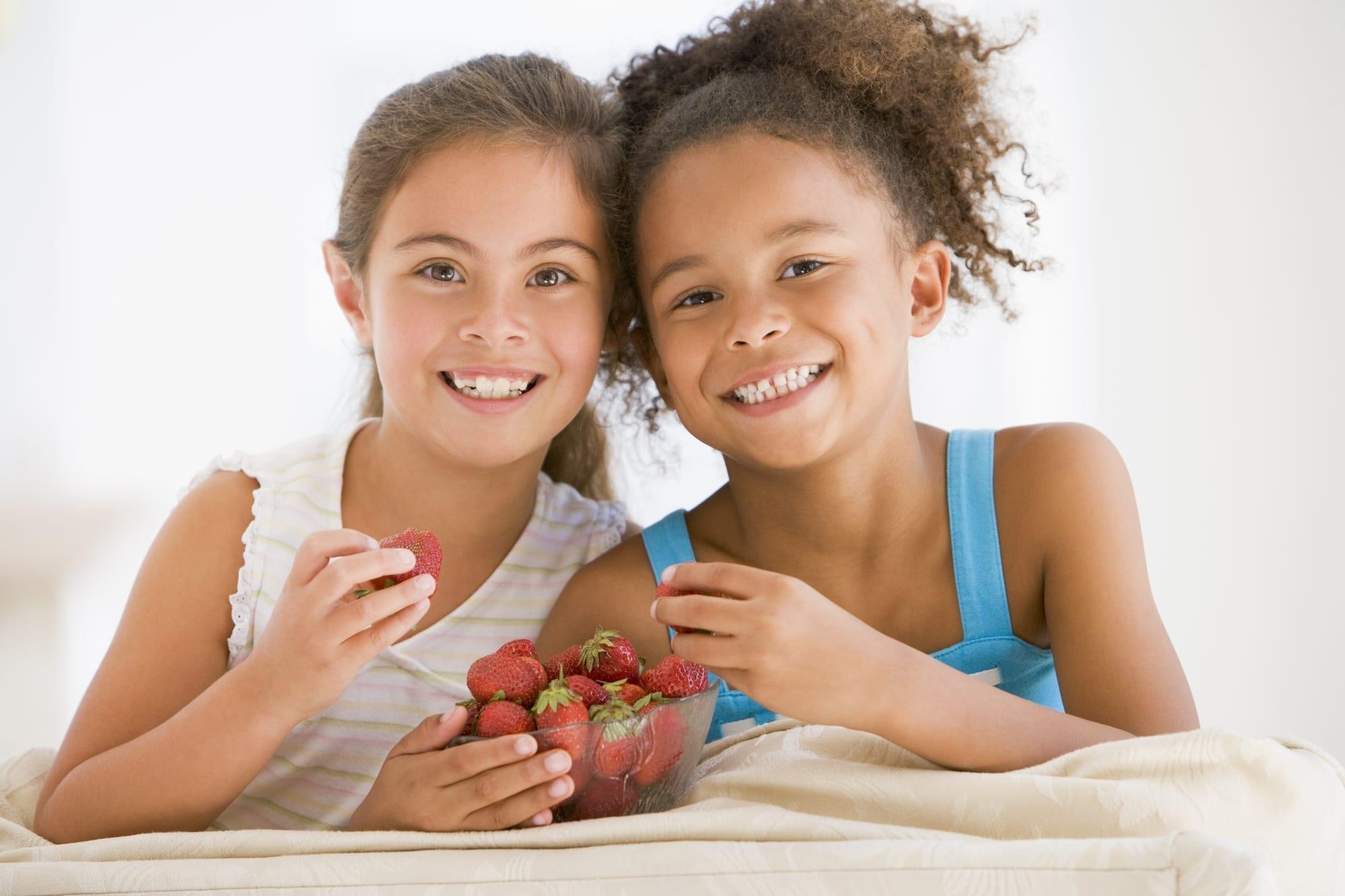 two little girls eating strawberries