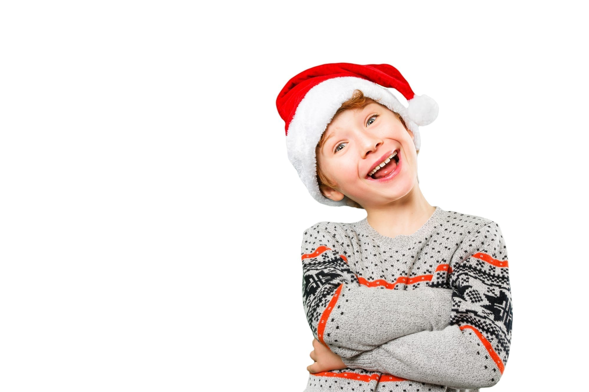 boy in santa hat smiling with arms crossed