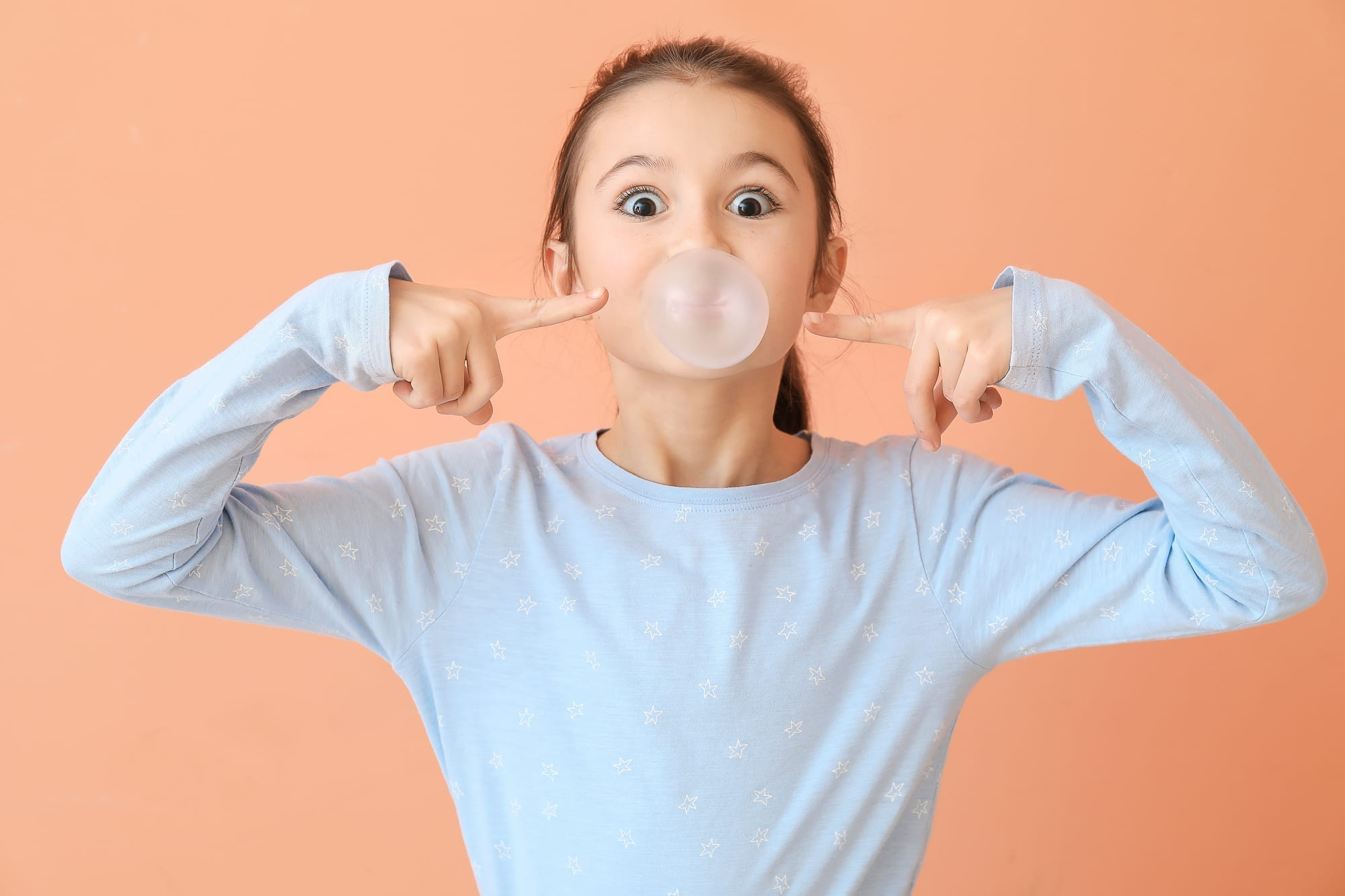 little girl blowing bubble with gum on peach background