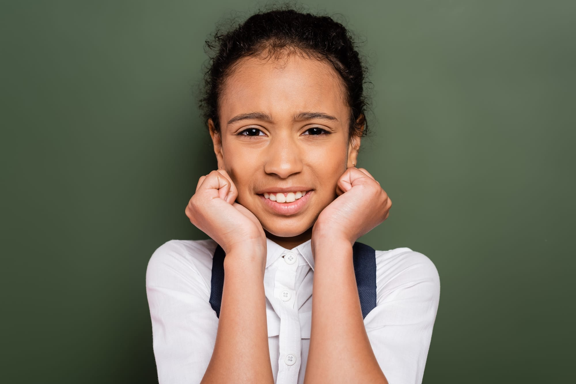 nervous young girl standing in front of green background