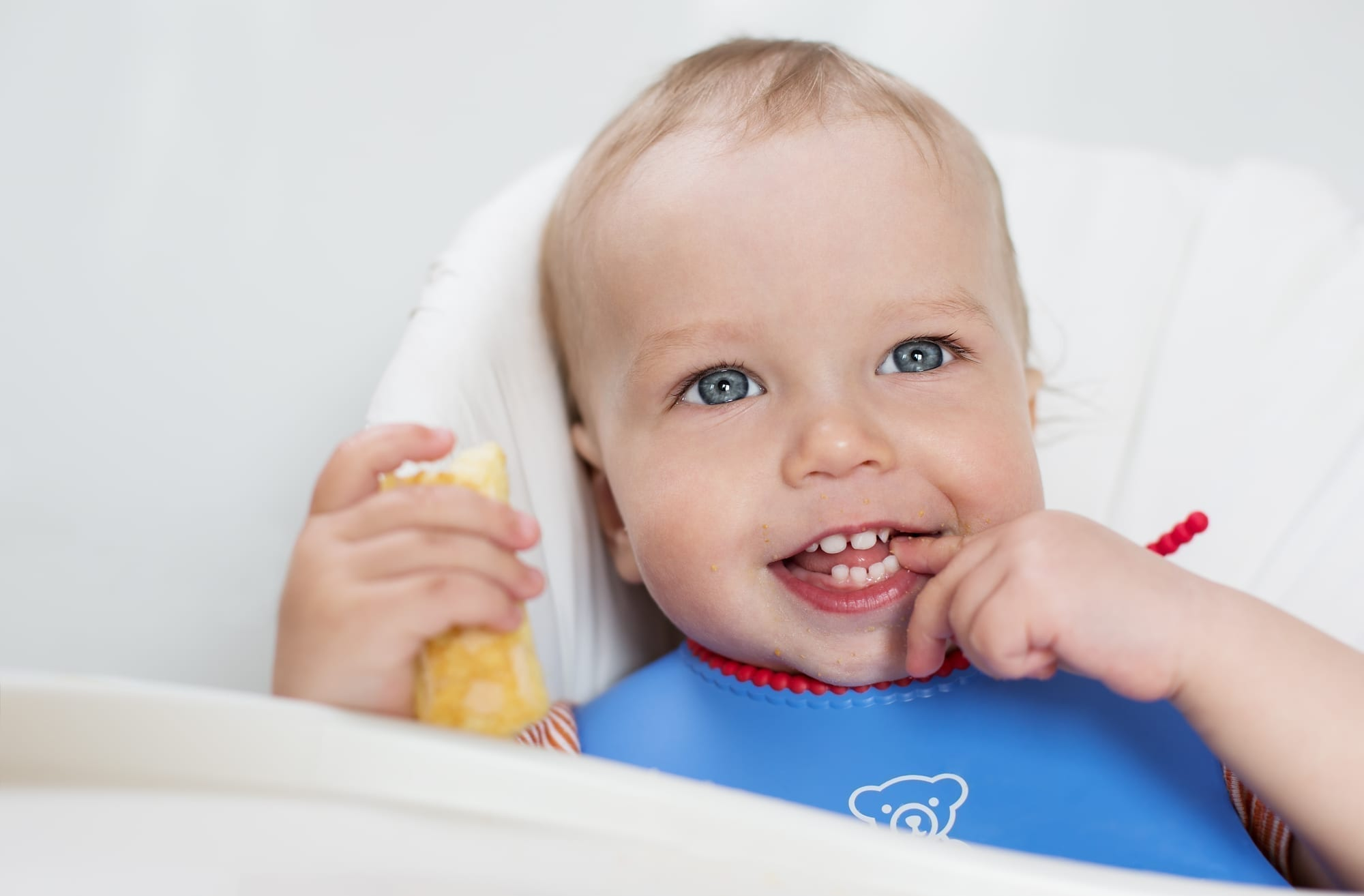 baby boy with blue eyes eating