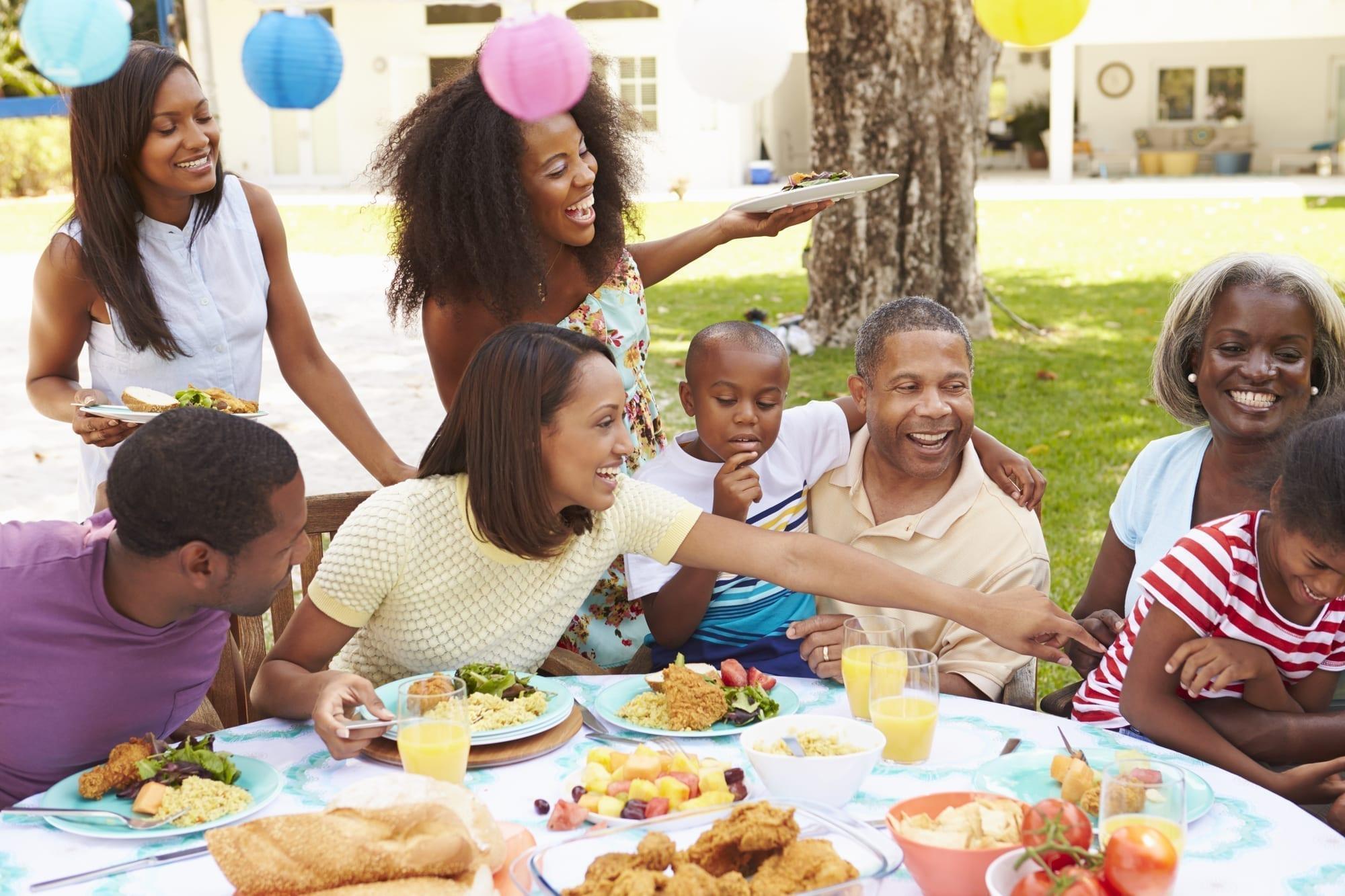 family laughing, eating, having part outside