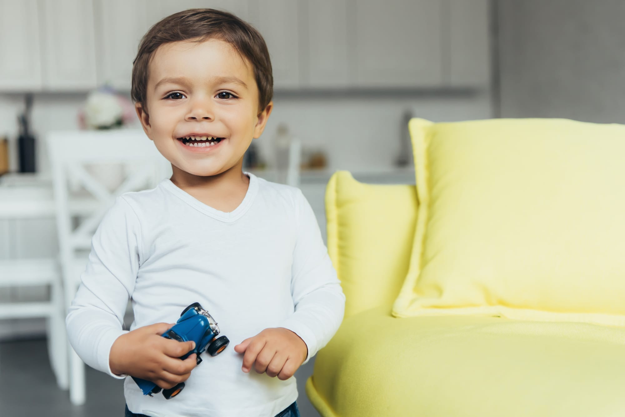 happy toddler with toy car