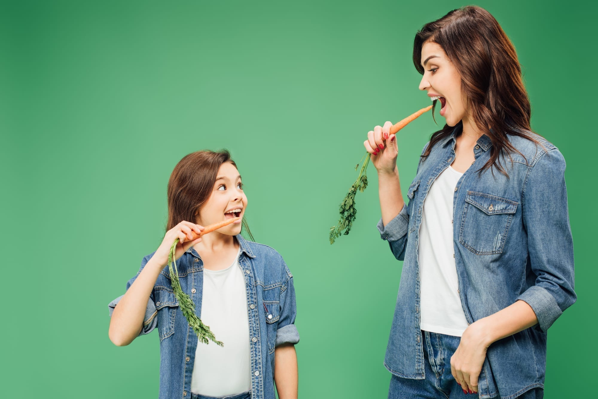 mom and daughter eating carrots on green background