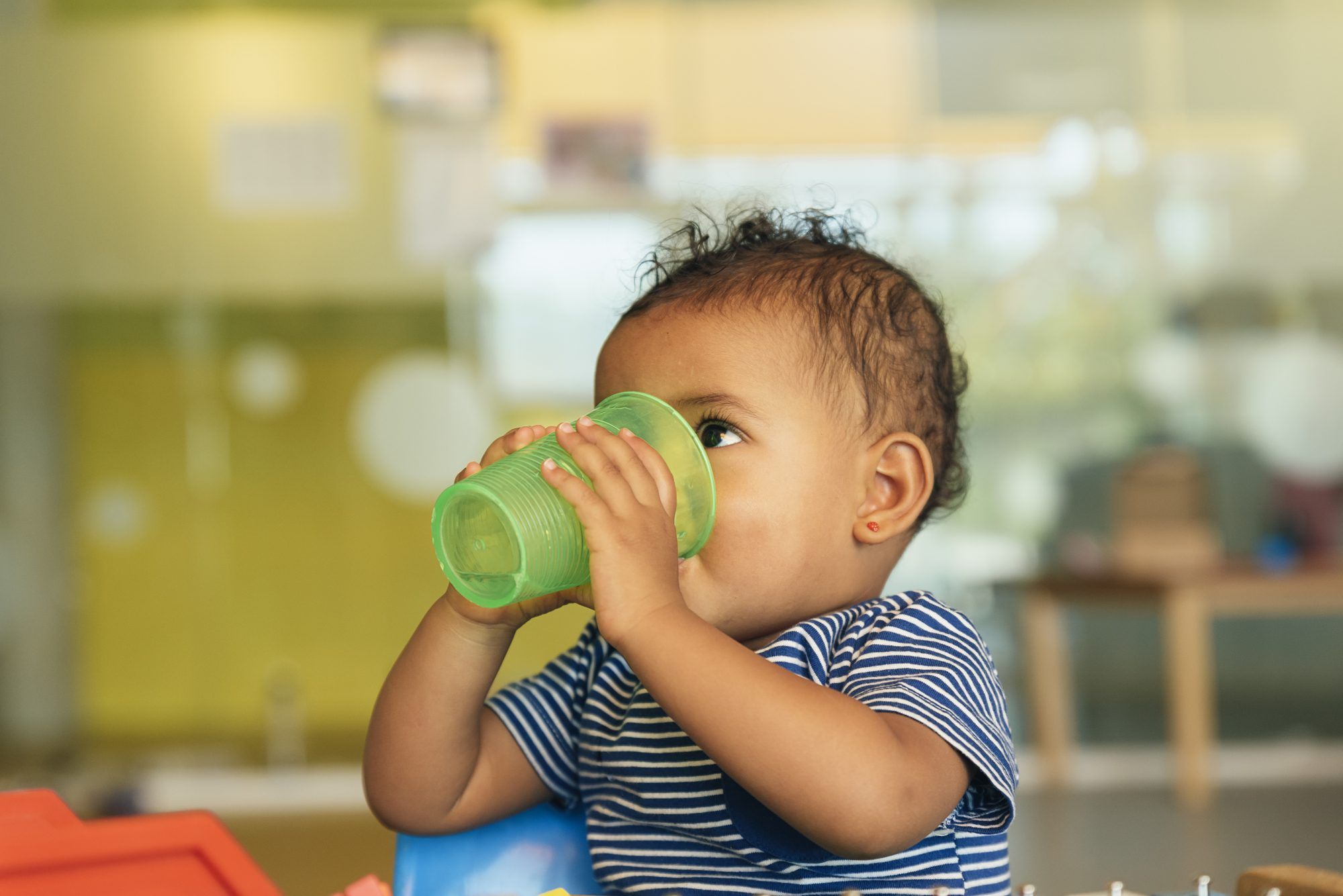 baby boy drinking water from a green cup