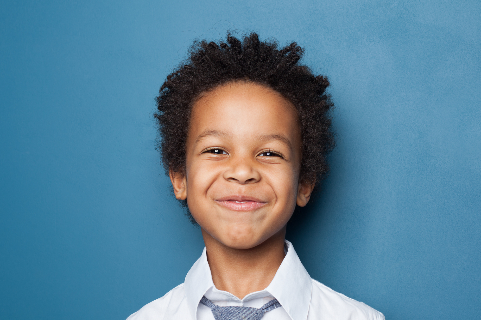 portrait of african american boy on blue background