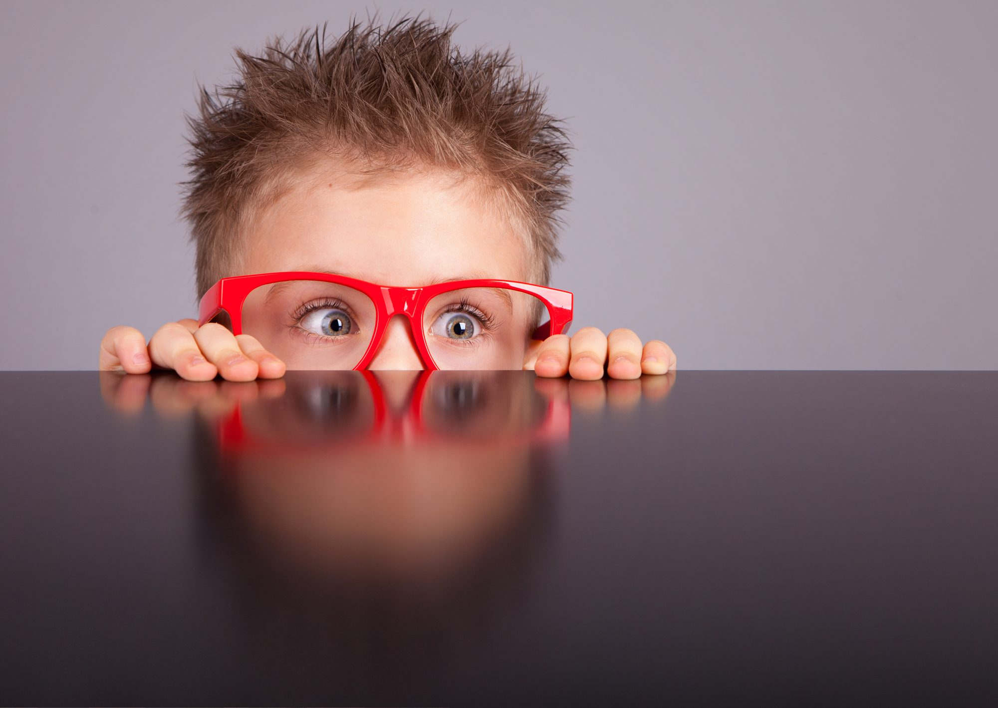 Anxious young boy hiding behind table with with red glasses
